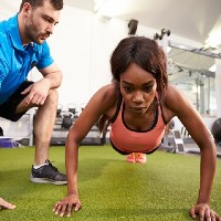 fitness trainer coaching a client who is doing push ups