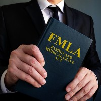 business man holding a family medical leave act book