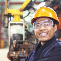 man smiling with a hard hat and safety glasses on