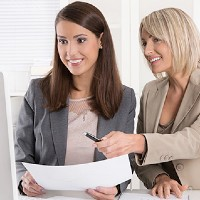 business woman showing another woman infromation on a computer and paper